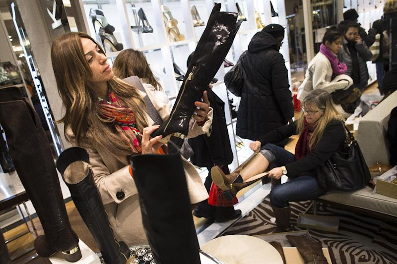 A shopper inspects a boot in the shoe section of the Macy's Herald Square flagship store, Thursday, Nov. 28, 2013, in New York. Instead of waiting for Black Friday, which is typically the year's biggest shopping day, more than a dozen major retailers are opening on Thanksgiving this year. (AP Photo/John Minchillo)