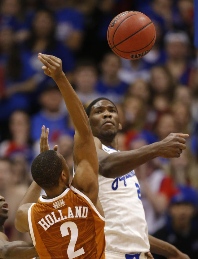 Kansas center Joel Embiid, right, blocks a shot by Texas guard Demarcus Holland (2) during the first half of an NCAA college basketball game in Lawrence, Kan., Saturday, Feb. 22, 2014. (AP Photo/Orlin Wagner)