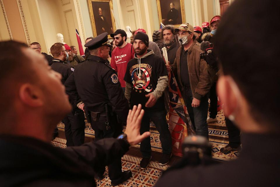 Trump supporters talk with Capitol Police inside the building.