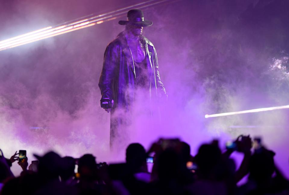 TOPSHOT - World Wrestling Entertainment star The Undertaker makes his way to the ring during a match at the World Wrestling Entertainment (WWE) Super Showdown event in the Saudi Red Sea port city of Jeddah late on January 7, 2019. (Photo by Amer HILABI / AFP)        (Photo credit should read AMER HILABI/AFP via Getty Images)