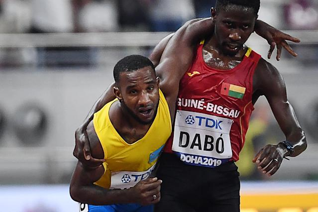 Guinea-Bissau's Braima Suncar Dabo, right, helps Aruba's Jonathan Busby to the finish line during the men's 5000 meter heats at the 2019 IAAF World Athletics Championships on Friday. (Getty Images)
