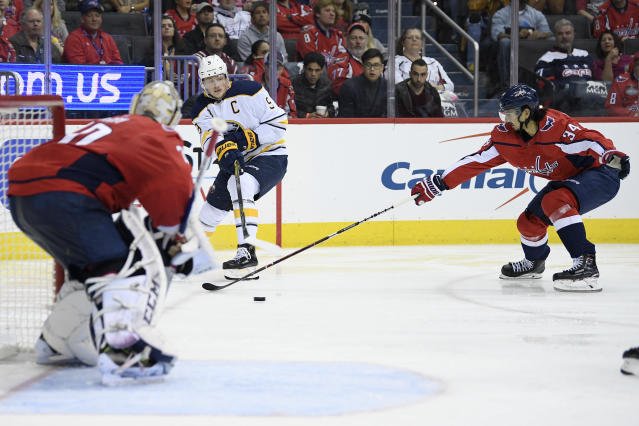Buffalo Sabres center Jack Eichel (9) passes the puck against Washington Capitals defenseman Jonas Siegenthaler (34) and goaltender Braden Holtby (70) during the second period of an NHL hockey game, Friday, Dec. 21, 2018, in Washington. (AP Photo/Nick Wass)