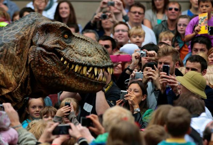 FILE PHOTO: Visitors photograph an animatronic Tyrannosaurus rex at the reopening of the National Museum of Scotland after its three-year £47 million redevelopment in Edinburgh