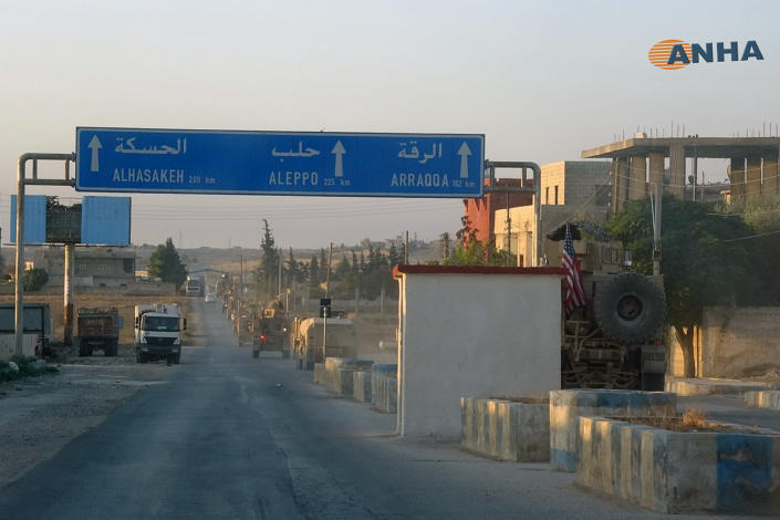 In this image provided by Hawar News Agency, ANHA, a line of U.S. military vehicles travel down a main road in northeast Syria, Monday, Oct. 7, 2019. U.S.-backed Kurdish-led forces in Syria said American troops began withdrawing Monday from their positions along Turkey's border in northeastern Syria, ahead of an anticipated Turkish invasion that the Kurds say will overturn five years of achievements in the battle against the Islamic State group. (ANHA via AP)