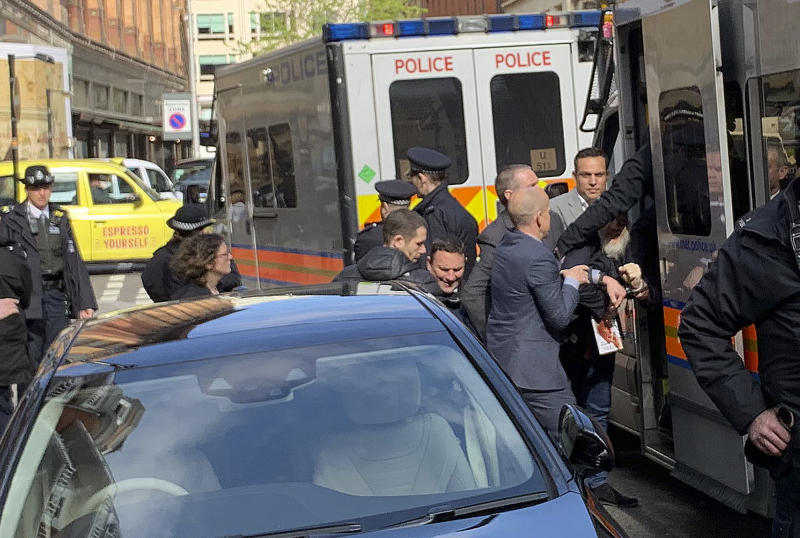 Police bundle WikiLeaks founder Julian Assange from the Ecuadorian embassy into a police van in London after he was arrested by officers from the Metropolitan Police and taken into custody Thursday April 11, 2019. Police in London arrested WikiLeaks founder Assange at the Ecuadorean embassy Thursday for failing to surrender to the court in 2012, shortly after the South American nation revoked his asylum. (@DailyDOOH via AP)