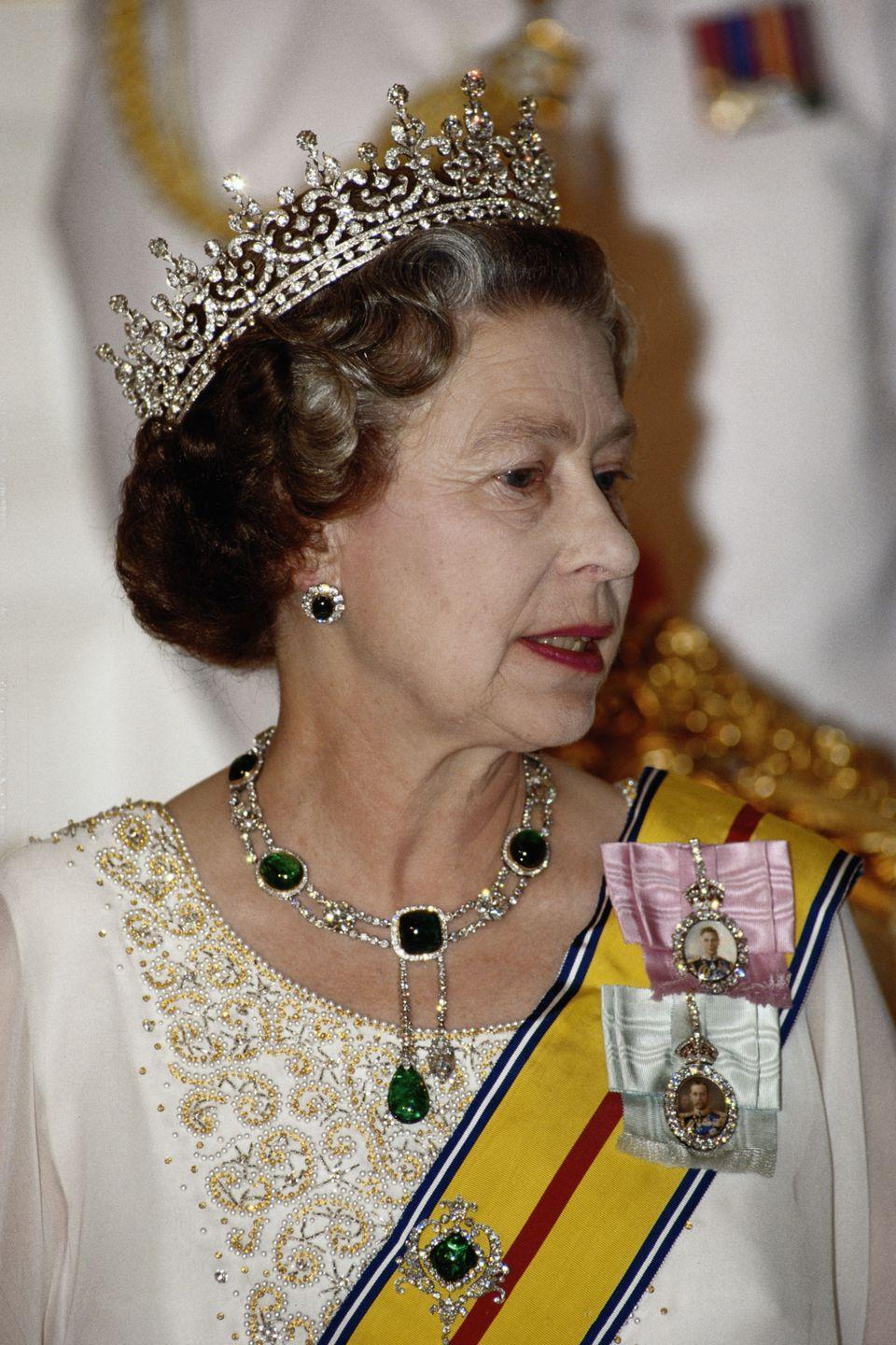 """<p>The Queen's emerald necklace and matching earrings, worn here on October 14, 1989, are known as the Cambridge and Delhi Durbar Parure. The tiara is Queen Mary's Girls of Ireland Tiara (also known affectionately as """"Granny's Tiara""""), which belonged to Elizabeth II's grandmother, Queen Mary. The tiara originally featured large pearls, which were removed on Queen Mary's orders and refashioned into the <a href=""""http://www.townandcountrymag.com/society/tradition/a10302981/cambridge-love-knot-tiara/"""" rel=""""nofollow noopener"""" target=""""_blank"""" data-ylk=""""slk:Cambridge Lover's Knot Tiara"""" class=""""link rapid-noclick-resp"""">Cambridge Lover's Knot Tiara</a>, a favorite of both Princess Diana and Katherine, the Duchess of Cambridge.</p>"""