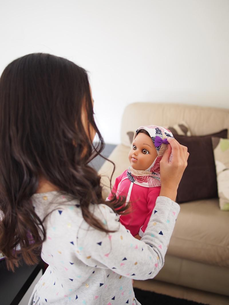 A young girl plays with a Salam Sisters doll named Maryam. (Salam Sisters / Zileej)