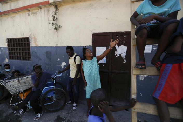 A woman orders her son to come down from a ladder at a shelter for displaced Haitians, in Port-au-Prince, Haiti, Saturday, July 10, 2021, three days after Haitian President Jovenel Moise was assassinated in his home. The displaced Haitians were forced to flee their community where they had settled after the 2010 earthquake, after armed gangs set their homes on fire in late June. (AP Photo/Fernando Llano)