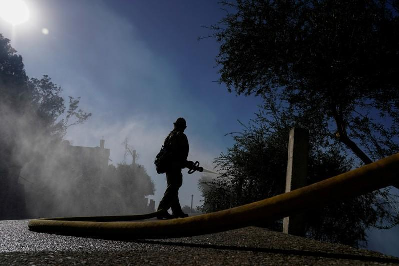 FILE PHOTO: A firefighter tackles the Dexter fire on a hillside near Riverside