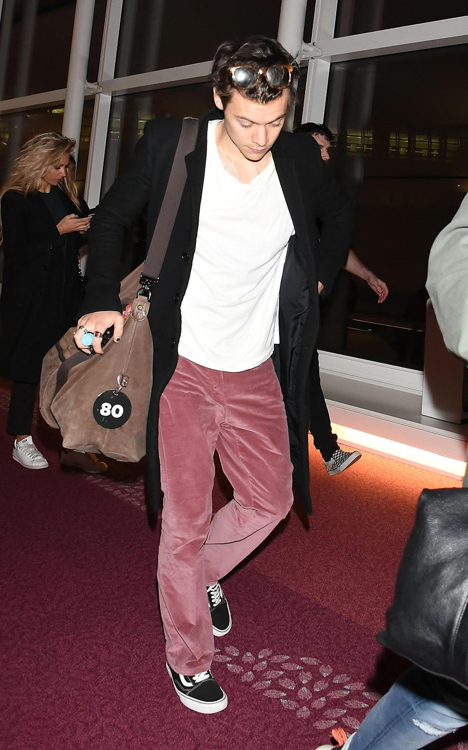 <p>At the airport in 2017 styling pink suede pants with a pair of black Vans. </p>