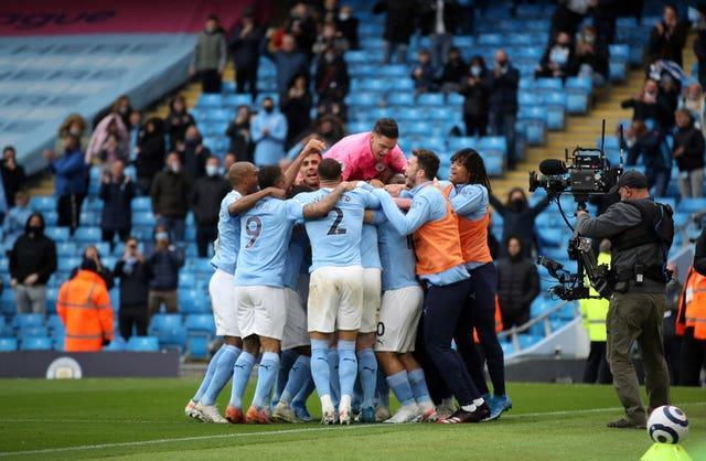 Manchester City's Sergio Aguero is mobbed by all of his team-mates after scoring