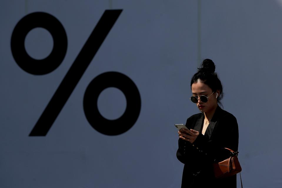 A Chinese woman wearing an Apple AirPods while browsing her iPhone past by a booth bearing a percent sign at the capital city's popular shopping mall in Beijing, Thursday, April 4, 2019. The U.S. and China opened a ninth round of talks on Wednesday, aiming to further narrow differences in an ongoing trade war that has deepened uncertainty for businesses and investors and cast a pall over the outlook for the global economy. (AP Photo/Andy Wong)