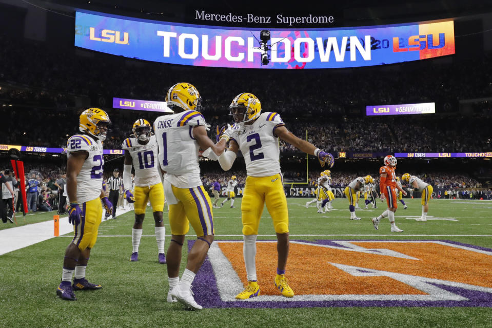 FILE - In this Jan. 13, 2020, file photo, LSU wide receiver Ja'Marr Chase (1) celebrates after scoring with wide receiver Justin Jefferson during the first half of a NCAA College Football Playoff national championship game against Clemson in New Orleans. There are more bowl games scheduled for the coming season than ever before in major college football: 42, not including the College Football Playoff championship. College football leaders are in the process of piecing together plans to attempt to play a regular season during the COVID-19 pandemic. If it is even possible, everyone anticipates there will be disruptions, added expenses and loads of stress just to get through it. (AP Photo/Gerald Herbert, File)