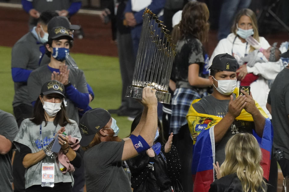 Los Angeles Dodgers third baseman Justin Turner celebrates with the trophy after defeating the Tampa Bay Rays 3-1 to win the baseball World Series in Game 6 Tuesday, Oct. 27, 2020, in Arlington, Texas. (AP Photo/Tony Gutierrez)