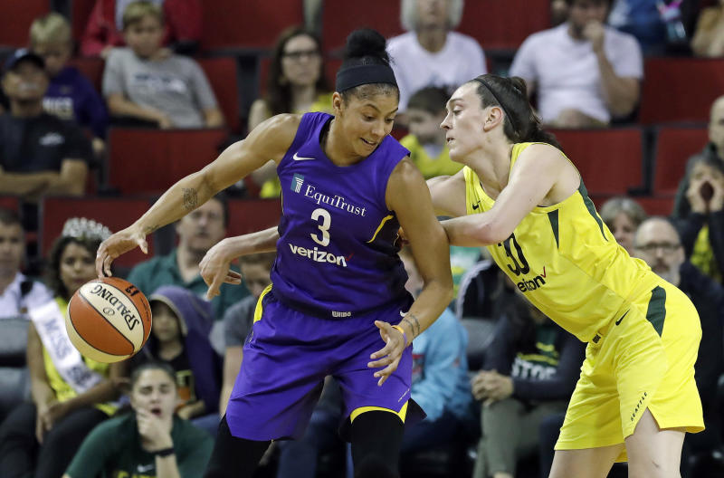 Seattle Storm's Breanna Stewart, right, is unsuccessful as she tries to reach around to grab the ball from Los Angeles Sparks' Candace Parker in the second half of a WNBA basketball game Tuesday, July 10, 2018, in Seattle. The Sparks won in overtime 77-75. (AP Photo/Elaine Thompson)