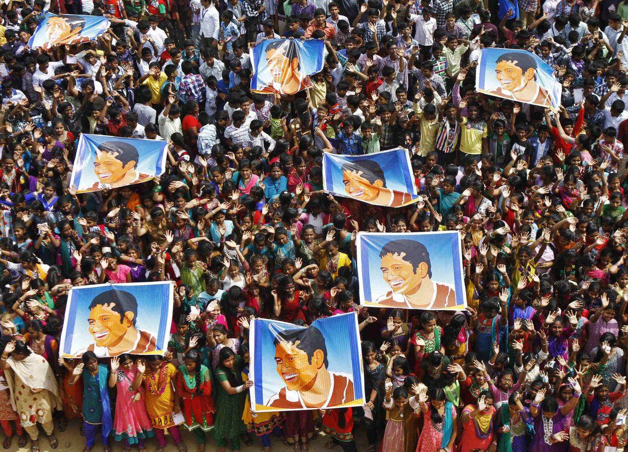 School children wave as they hold posters of Indian cricketer Sachin Tendulkar at an event to honour him inside a school in the southern Indian city of Chennai November 14, 2013. Cricket-crazy India will have a lump in the throat as its favourite son, Tendulkar, walks out for one last time this week to play the game he has dominated for nearly a quarter of a century. The 'Little Master' will bring the curtain down on a glittering 24-year career at the age of 40 when he plays his 200th test match, against West Indies, at his home ground starting on Thursday. REUTERS/Babu (INDIA - Tags: SPORT CRICKET TPX IMAGES OF THE DAY)
