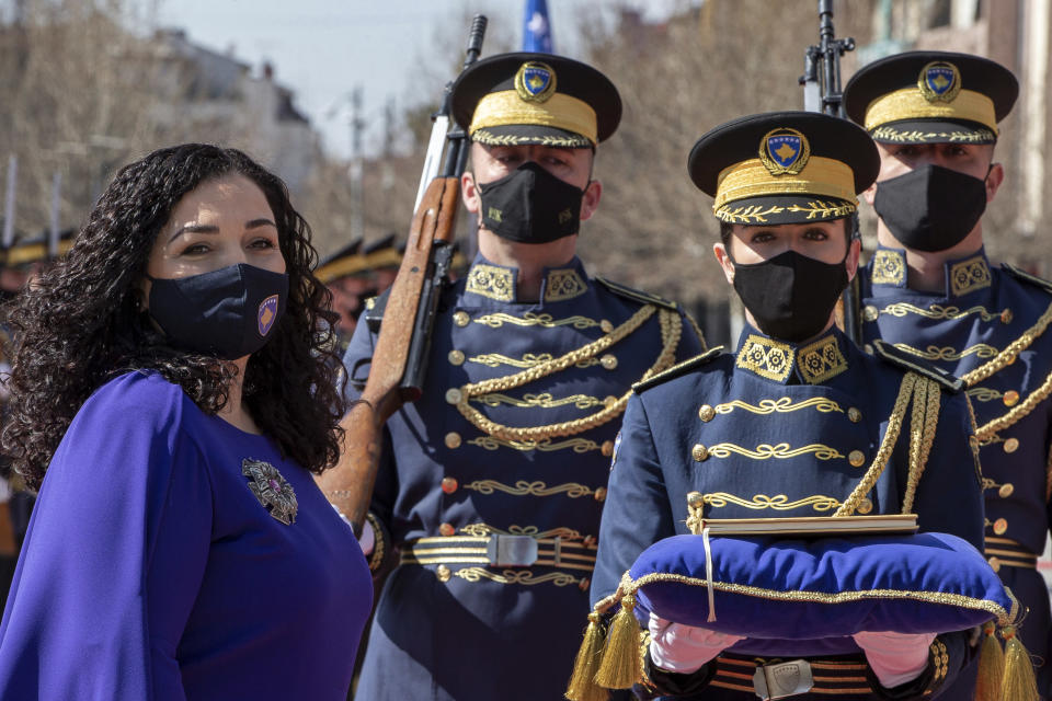 Kosovo newly elected president Vjosa Osmani-Sadriu, as Guard of Honour presents the Kosovo Constitution during a presidential hand over ceremony in capital Pristina, Kosovo, on Tuesday, April 6, 2021. 38-year old Osmani took over the presidency after being elected to the post during a two-day extraordinary session of parliament. (AP Photo/ Visar Kryeziu)