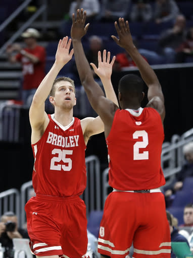 Bradley's Nate Kennell (25) is congratulated by teammate Luqman Lundy (2) after making a 3-point basket during the first half of an NCAA college basketball game against Loyola of Chicago in the semifinal round of the Missouri Valley Conference tournament, Saturday, March 9, 2019, in St. Louis. (AP Photo/Jeff Roberson)