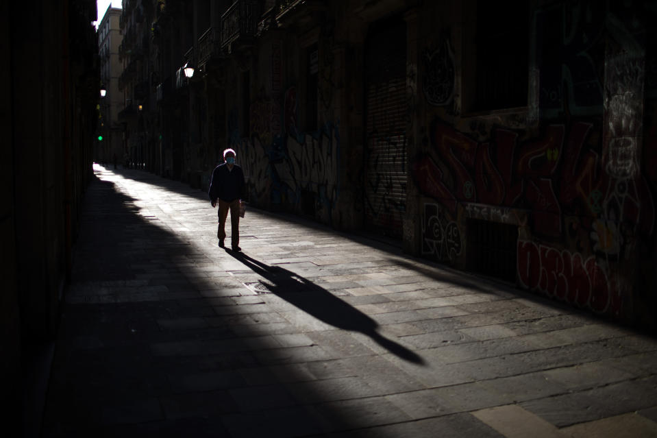 A man walks along an empty street in downtown Barcelona, Spain, Saturday, April 25, 2020 as the lockdown to combat the spread of coronavirus continues. (AP Photo/Emilio Morenatti)