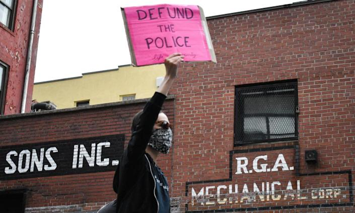 A woman holds a placard reading 'Defund the Police' during a demonstration in Manhattan over the death of George Floyd.