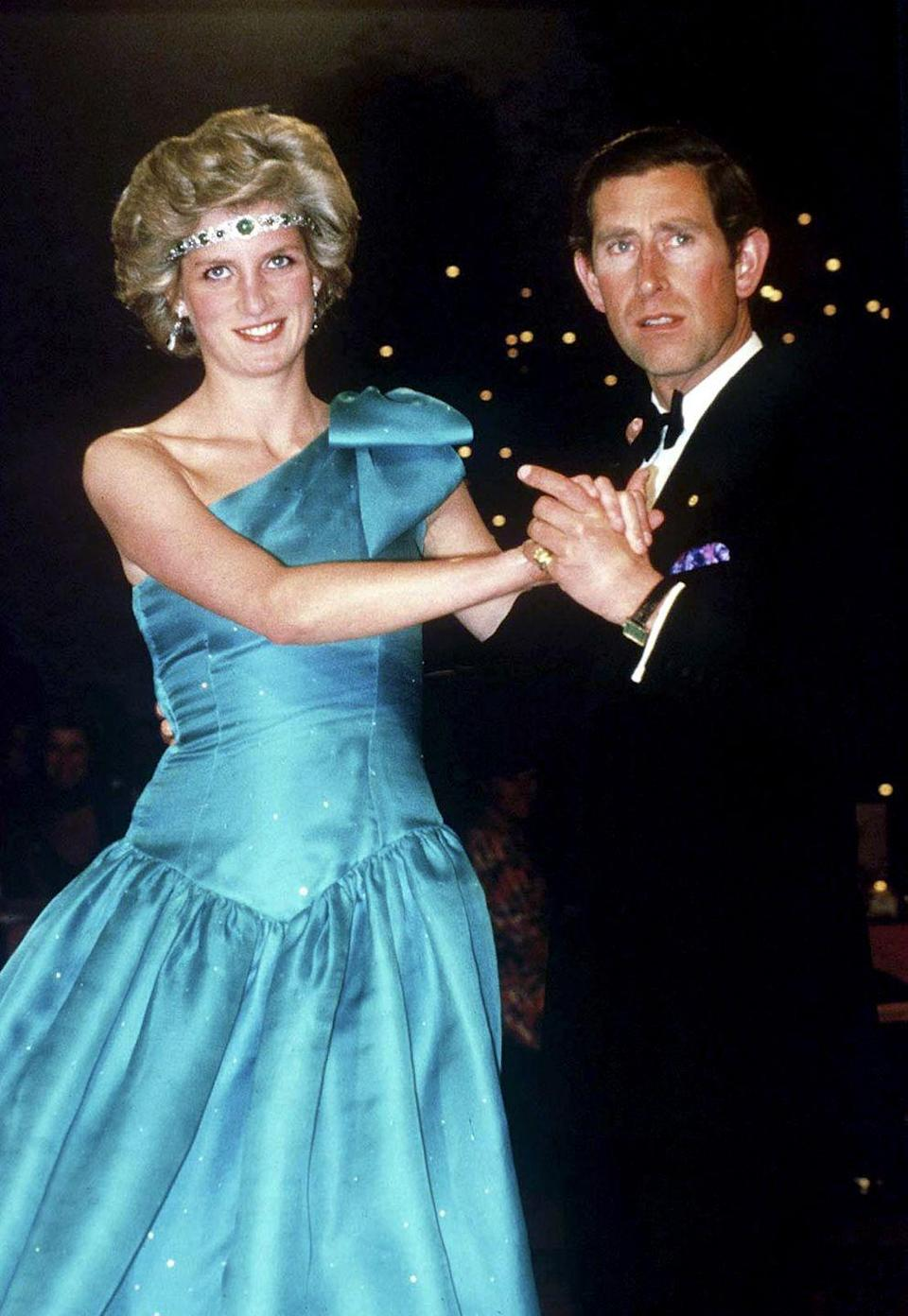 <p>Princess Diana danced with Prince Charles in Melbourne, during their official tour of Australia. Here, Diana went for a more unconventional tiara look: she took a diamond and emerald choker necklace, which had been a wedding gift from the Queen, and turned it into a headpiece. She paired the tiara-of-sorts with a one-shouldered turquoise gown, designed by the Emmanuels. </p>