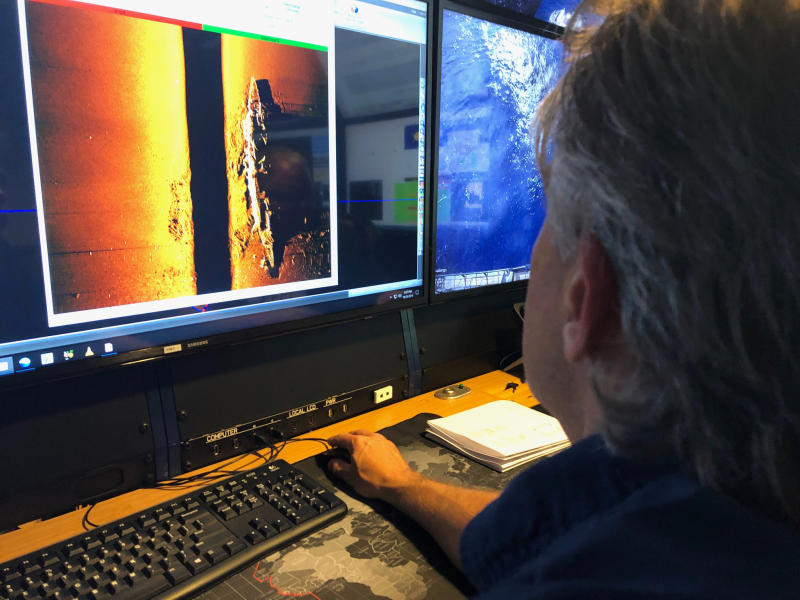A man seen looking at images of the sunken vessel on a computer screen.