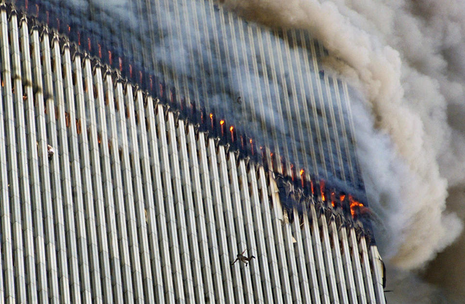 <p>A person falls from the north tower of New York's World Trade Center as another clings to the outside, left, while smoke and fire billow from the building, Tuesday Sept. 11, 2001. (AP Photo/Richard Drew)</p>