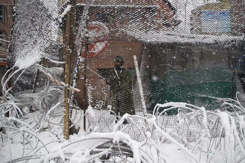 An Indian paramilitary soldiers removes snow from a net protecting their bunker in Srinagar, Indian controlled Kashmir, Thursday, Feb. 7, 2019. The fresh snowfall has resulted in disruption of air and road traffic for the second consecutive day between Srinagar and Jammu, the summer and winter capitals of India's troubled state. (AP Photo/ Dar Yasin)