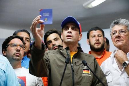 Venezuelan opposition leader and Governor of Miranda state Henrique Capriles (C) holds a copy of the Venezuelan Constitution as he speaks during a news conference in Caracas, Venezuela, April 6, 2017. REUTERS/Carlos Garcia Rawlins