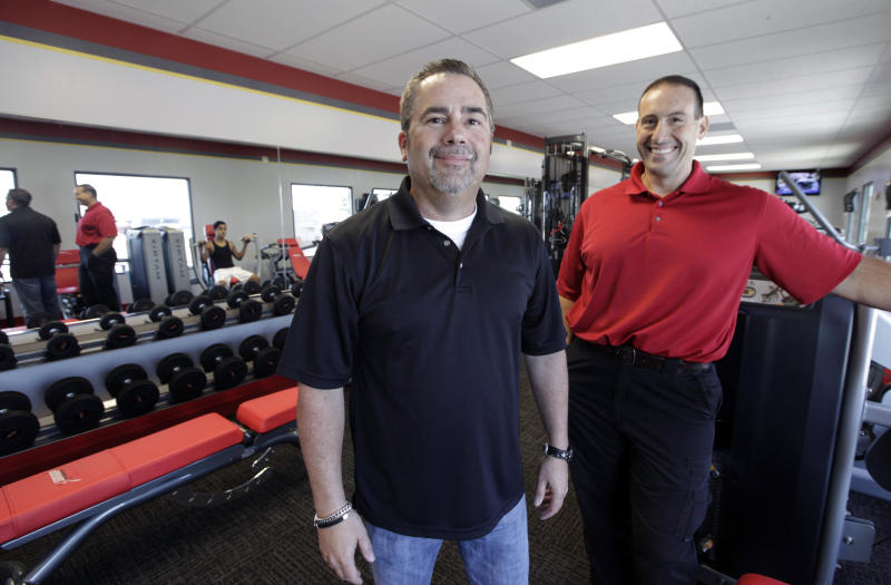 In this June 14, 2012, photo, Gary Findley, Chief Operating Officer of Snap Fitness, left, and Rick Limitone, manager of a Snap Fitness gym, pose for a photo at the truck stop location in Dallas. From trucking companies embracing wellness and weight-loss programs to gyms being installed at truck stops, momentum has picked up in recent years to help those who make their living driving big rigs get into shape. (AP Photo/LM Otero)