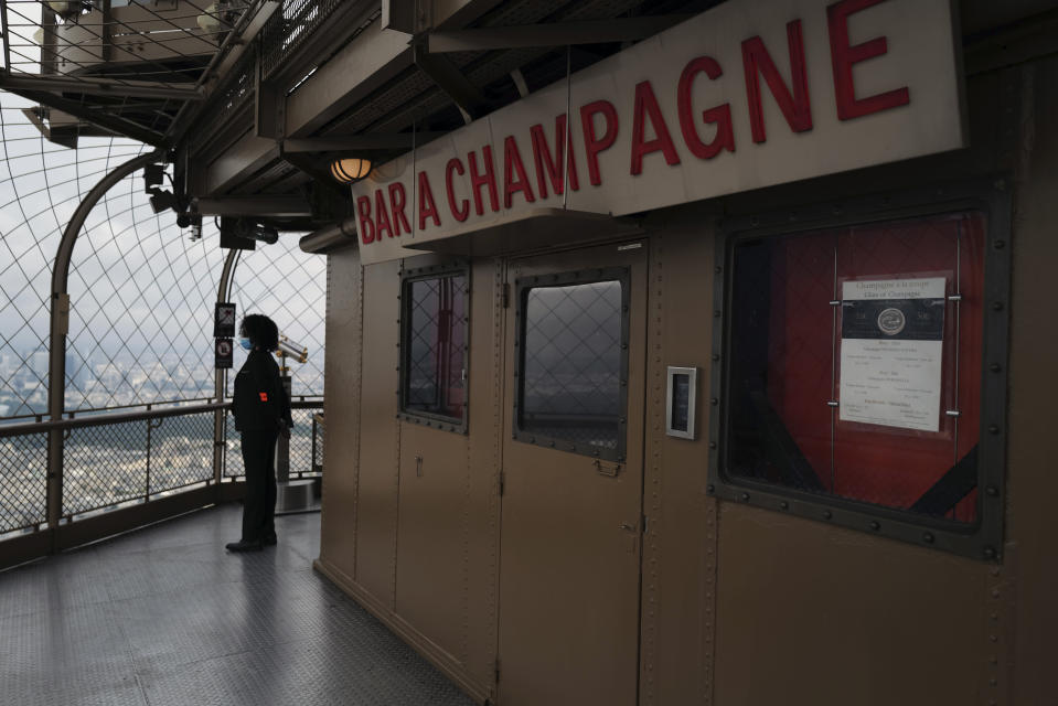 French security officer looks on next to the Champagne Bar of the third level, during the opening up of the top floor of the Eiffel Tower, in Paris, Wednesday, July 15, 2020. The top floor of Paris' Eiffel Tower reopened today as the 19th century iron monument re-opened its first two floors on June 26 following its longest closure since World War II. (AP Photo/Francois Mori)