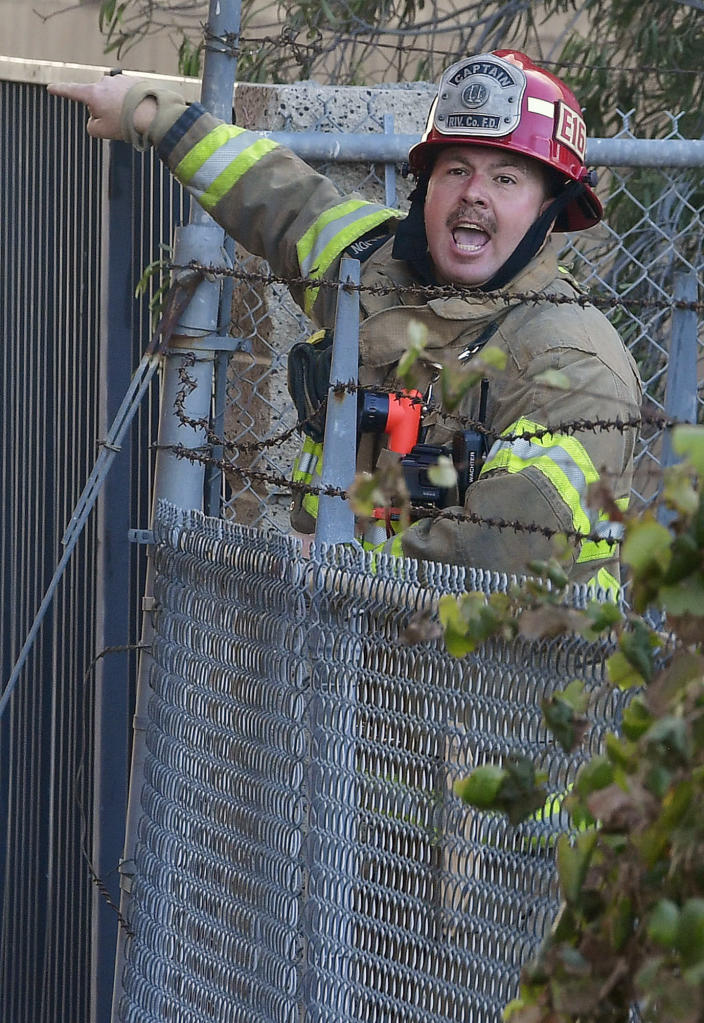 A Riverside County fire captain yells for firefighters to advance their hose line as they battle a mulch and pallet fire burning out of control, fanned by Santa Ana winds in and around a recycling yard near Wilson Street and Fleetwood Drive in Riverside, Calif., Thursday, Dec. 3, 2020. Firefighters from both Riverside and San Bernardino County, along with assistance from Colton, Rialto and Riverside City Fire fought the blaze. (Will Lester/The Orange County Register via AP)