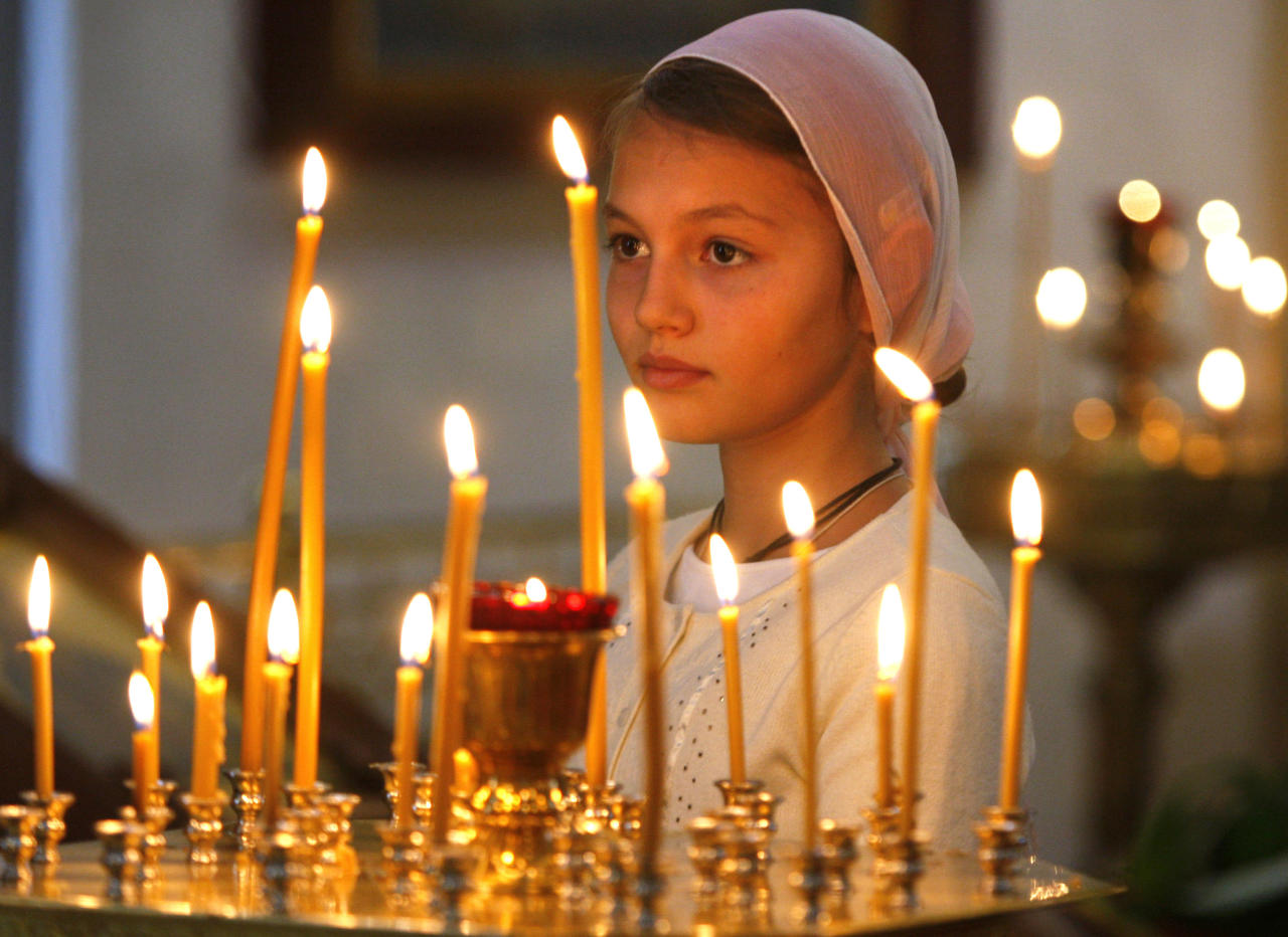 A girl attends an Orthodox service at St. Catherine in remembrance of the victims of the Sept. 11, 2001 terror attacks, Moscow, Sunday, Sept. 11, 2011. Sunday marks the tenth anniversary of the attacks of September 11, 2001. (AP Photo/Sergei Grits)