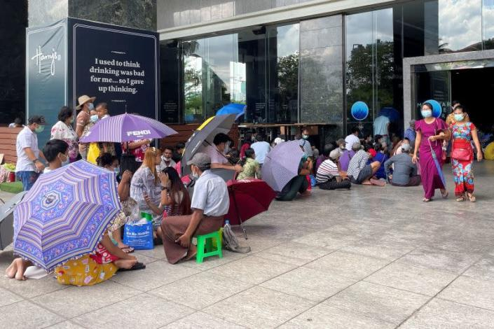 People line up outside a bank to withdraw cash, in Yangon