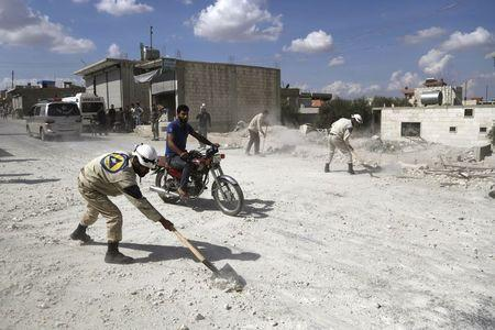 Civil defence members remove rubble from a site hit by what activists said were airstrikes carried out by the Russian air force in Kafranbel, near Idlib Syria October 10, 2015. REUTERS/Khalil Ashawi