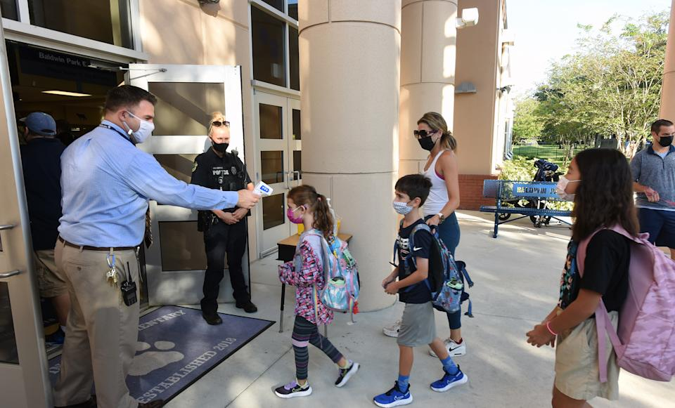 Principal Nathan Hay performs temperature checks on students as they arrive on the first day of classes for the 2021-22 school year at Baldwin Park Elementary School. (Paul Hennessy/SOPA Images/LightRocket via Getty Images)
