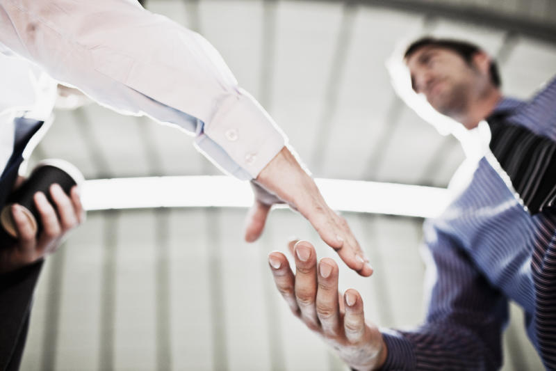 Two men in professional attire shaking hands.