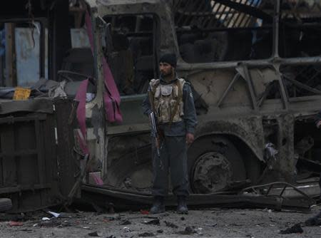 An Afghan policeman stands guard in front of a destroyed bus after the blast in Kabul