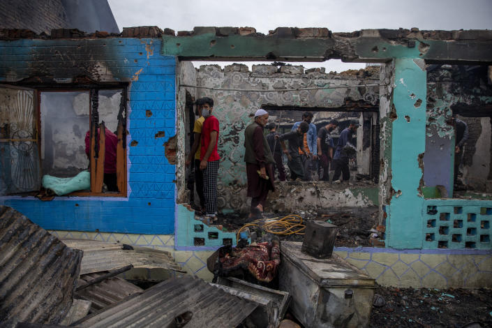 Kashmiri villagers stand inside a house destroyed in a gunfight in Pulwama, south of Srinagar, Indian controlled Kashmir, Wednesday, July 14, 2021. Three suspected rebels were killed in a gunfight in Indian-controlled Kashmir on Wednesday, officials said, as violence in the disputed region increased in recent weeks. Two residential houses were also destroyed. (AP Photo/ Dar Yasin)