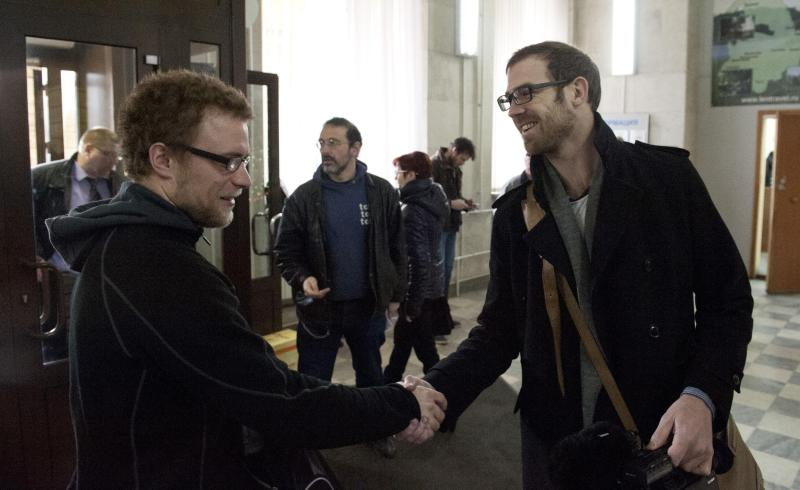 Greenpeace handout shows Greenpeace International activists Weber and videographer Bryan congratulating each other, after having criminal charges against them dropped, in Saint Petersburg