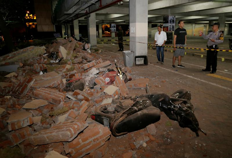 A policeman examines debris that fell and crushed parked motorbikes following a strong earthquake on nearby Lombok island, at a shopping center in Kuta, Bali, Indonesia  August 5, 2018. REUTERS/Johannes P. Christo