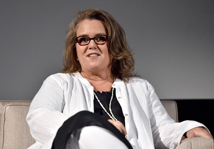 Rosie sits on stage at an event