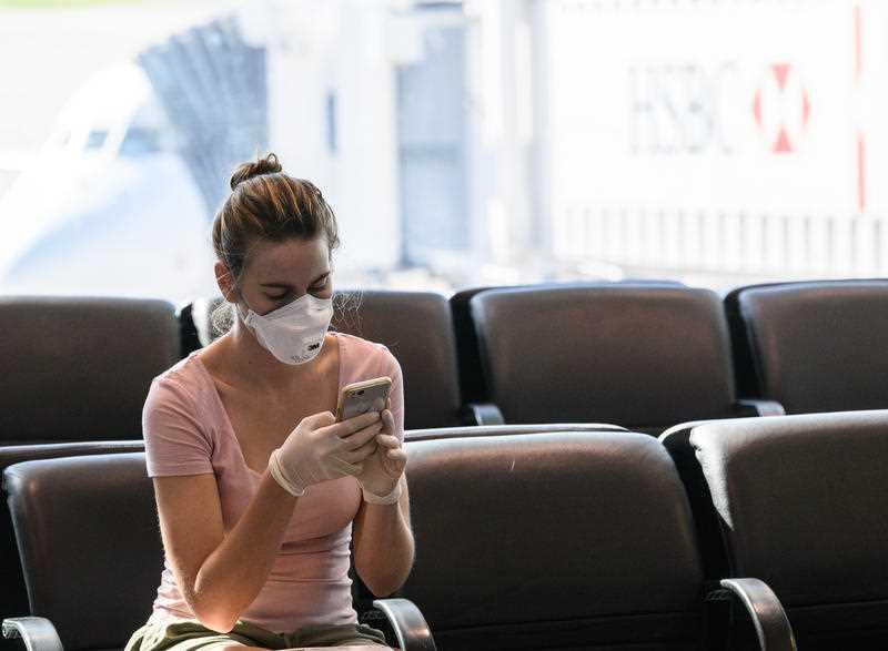 A woman wearing a face mask and gloves looks at her phone at Sydney Airport.