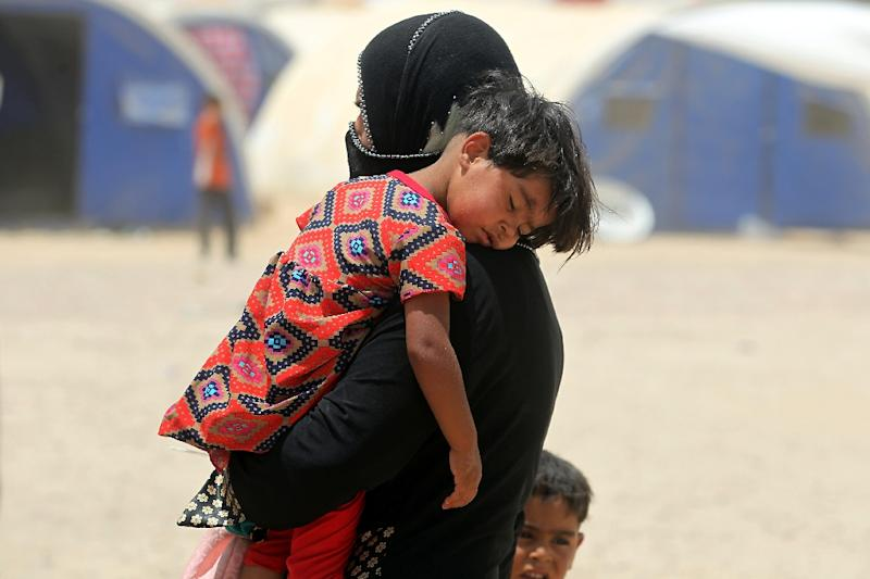 An Iraqi woman displaced from the city of Fallujah carries a child at a newly opened camp where hundreds of Iraqis are taking shelter in Amriyat al-Fallujah on June 27, 2016 Iraqi forces on June 26 wrapped up operations in Fallujah and declared the area free of jihadists from the Islamic State (IS) group after a month-long operation. The government said the destruction caused by the fighting was limited and vowed to do its utmost to allow the tens of thousands of displaced civilians to return to their homes. (AFP Photo/Ahmad Al-Rubaye)