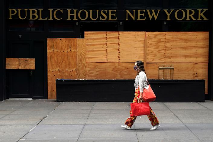 A woman walks past a shuttered bar following the coronavirus disease outbreak in the Manhattan borough of New York City, New York, U.S., August 7, 2020. REUTERS/Carlo Allegri