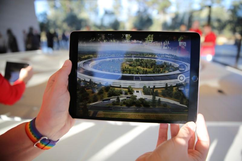 FILE PHOTO - An Apple employee uses an iPad with an augmented reality app on it to show off features of the new Apple Park at the Apple Visitor Center in Cupertino