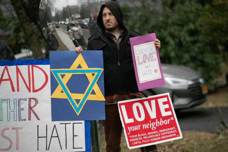 A man holds a sign outside the home of rabbi Chaim Rottenberg in Monsey