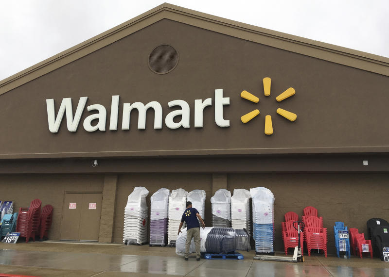 FILE - In this June 5, 2017, file photo, a worker stacks merchandise outside a Walmart in Salem, N.H. Walmart is boosting its starting salary for U.S. workers to $11 an hour, giving a one-time $1,000 cash bonus to eligible employees and expanding its maternity and parental leave benefits. The retailer said Thursday, Jan. 11, 2018, changes to its compensation and benefits policy will impact more than a million hourly workers in the U.S., with the wage increase effective next month. (AP Photo/Elise Amendola, File)