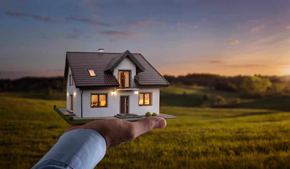 Concept of buying or building a new home. Male hand showing, offering a new dream house at the empty field with copy space