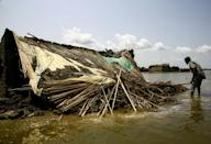 A South Sudanese refugee inspects a house damaged in floods in Al-Qanaa village in Sudan's southern White Nile state (AFP/ASHRAF SHAZLY)